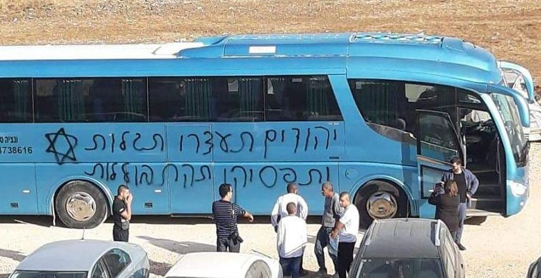 """One of the messages scrawled on the side of a bus in Jaljulia reads: """"Jews, end the diaspora [mindset] and stop assimilating."""""""