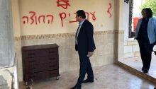 "Echoes of another time, another place: Hadash MK's Ayman Odeh and Aida Touma-Sliman during a solidarity visit to the village of Manshiya Zabda on Thursday, December 12. The Hebrew graffiti spray painted on the wall reads: ""Arabs out."""