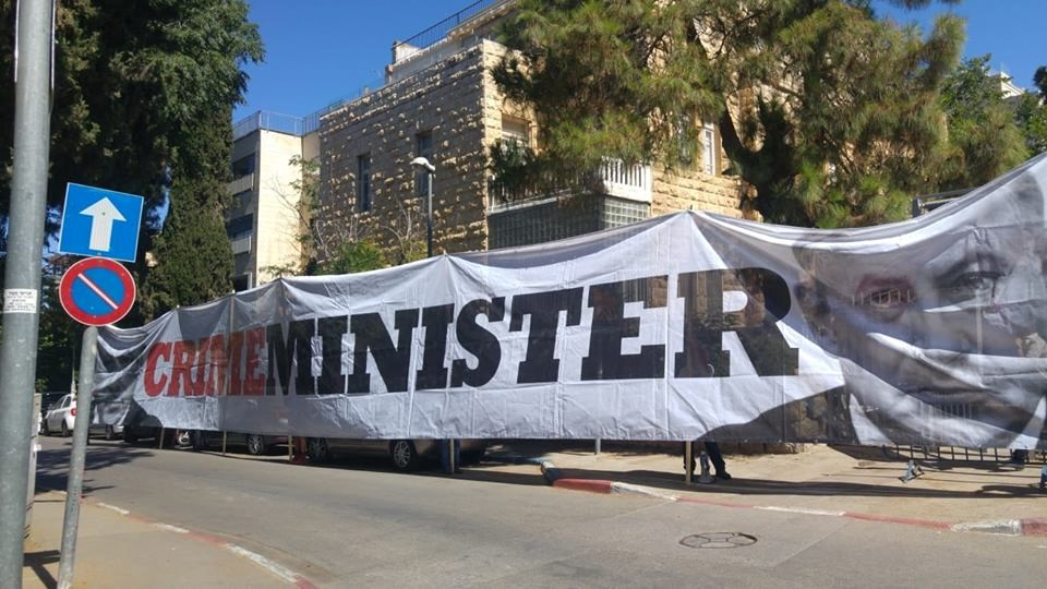 """""""Crime Minister,"""" a banner displayed by protestors near Prime Minister Benjamin Netanyahu's official residence on Balfour Street in Jerusalem"""