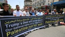 "Palestinians demonstrate in Ramallah in late June 2019 during the then ongoing ""Peace to Prosperity"" workshop, initiated by the Trump administration, taking place in Bahrain. The slogan in Arabic at the top of the banners reads: ""Down with the Deal of the Century.. Down with the Bahrain Workshop."""