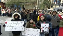 "A demonstration held in Majdal Shams against Israeli plans for a commercial wind farm that would see at least 25 turbines built in the occupied Syrian territory. The placard in Arabic on the right reads: ""The roots of our trees are stronger than your wind turbines""; the sign on the left says: ""Because I want my daughter to be among the apple trees when I die."""