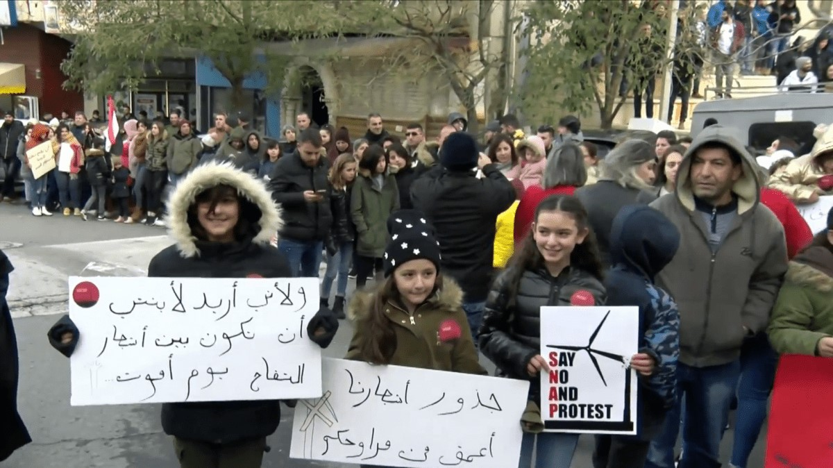 """A demonstration held in Majdal Shams against Israeli plans for a commercial wind farm that would see at least 25 turbines built in the occupied Syrian territory. The placard in Arabic on the right reads: """"The roots of our trees are stronger than your wind turbines""""; the sign on the left says: """"Because I want my daughter to be among the apple trees when I die."""""""