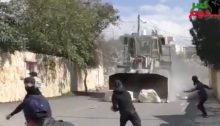 An armored Israeli military bulldozer pushes massive slabs of stone at speed towards Palestinian protesters in Kafr Qaddum, near Qalqilia in the occupied West Bank. Friday, February 21.