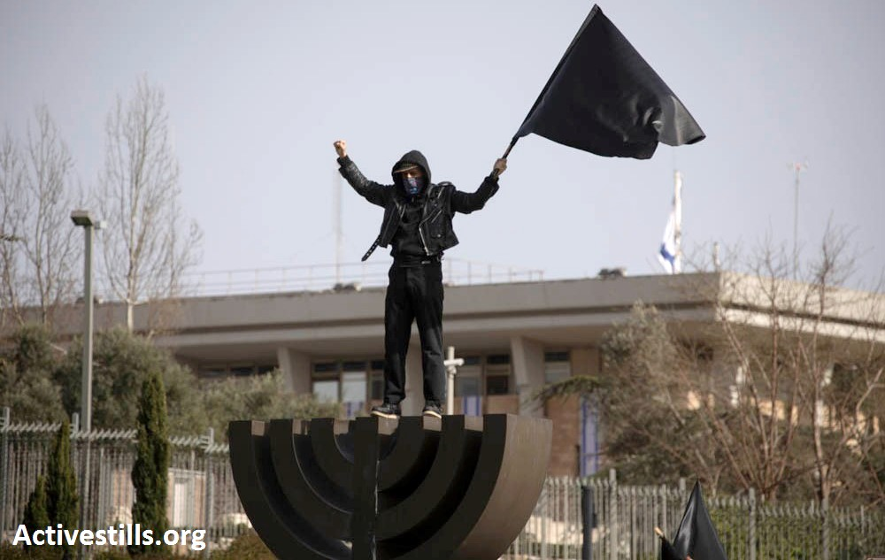 One of the thousand protesters who gathered outside the Knesset in Jerusalem on Wednesday, March 25, to protest the anti-democratic measures adopted by Netanyahu's far-right government