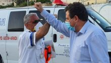 Joint List chairman, MK Ayman Odeh (Hadash) and a paramedic greet one another in the village of Bi'ina village in the Galilee, Monday, April 13.