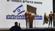 "MK Ayman Odeh addresses protesters in the rally held Sunday evening in Central Tel-Aviv. The backdrop behind him reads: ""Black Flag Protest – Fighting for Democracy."""