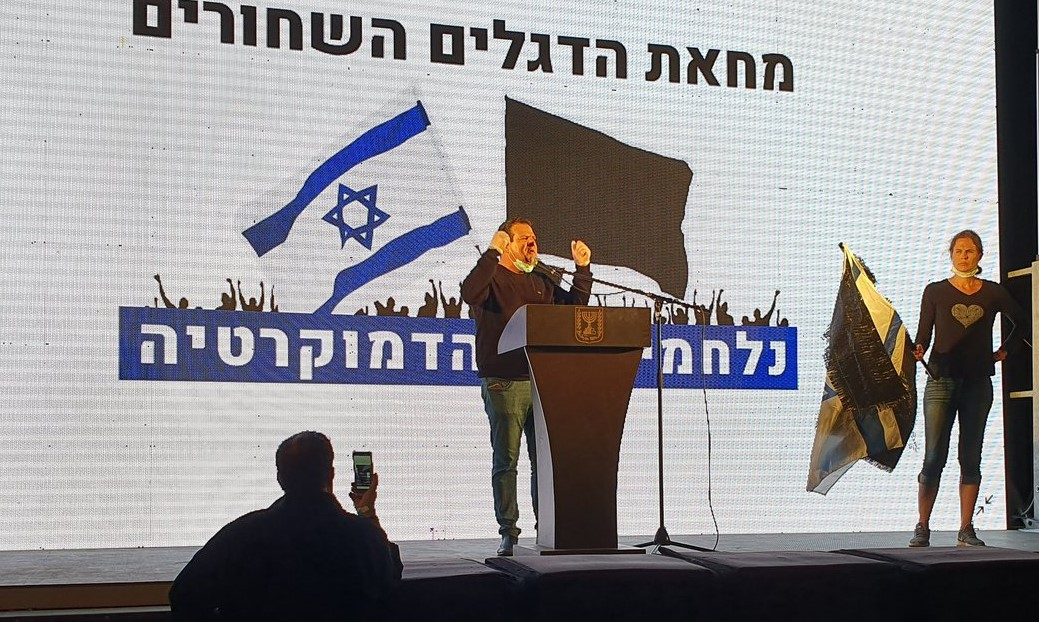 """MK Ayman Odeh addresses protesters in the rally held Sunday evening in Central Tel-Aviv. The backdrop behind him reads: """"Black Flag Protest – Fighting for Democracy."""""""