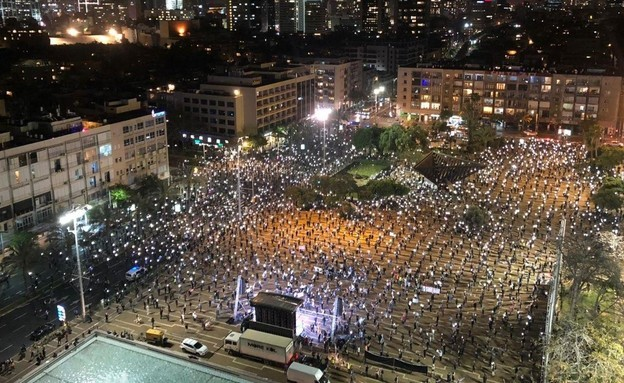"""While adhering to social distancing regulations, thousands participate in a """"Black Flag Protest"""" that was held Sunday evening, April 19, in Rabin Square in Central Tel Aviv."""
