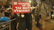 "Two of the Hadash activists who participated in the demonstration organized by the Black Flag Movement on Saturday evening, April 25, Tel Aviv's Rabin Square; the Hadash placard reads ""When the government is against the people, the people are against the government."""