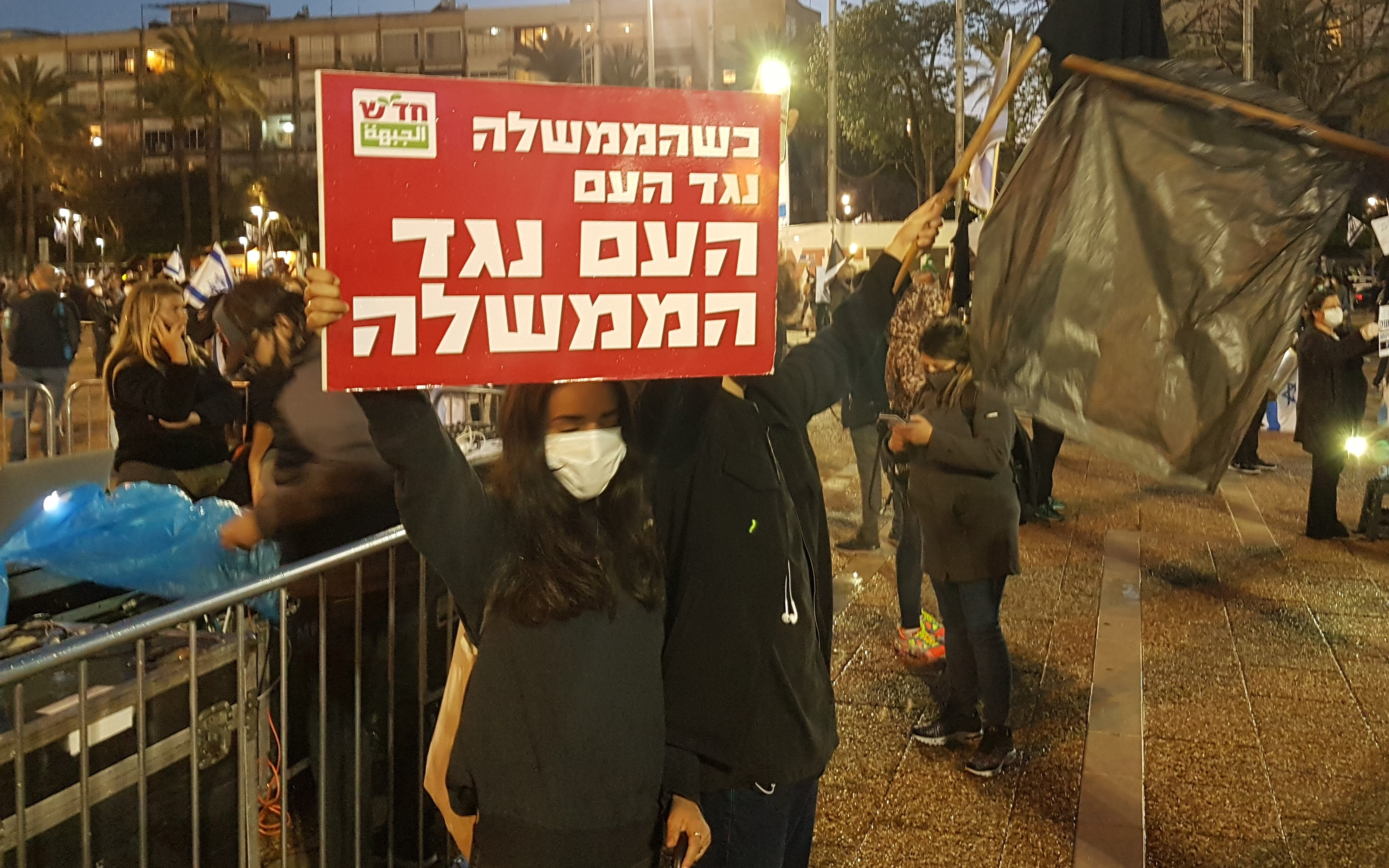 """Two of the Hadash activists who participated in the demonstration organized by the Black Flag Movement on Saturday evening, April 25, Tel Aviv's Rabin Square; the Hadash placard reads """"When the government is against the people, the people are against the government."""""""