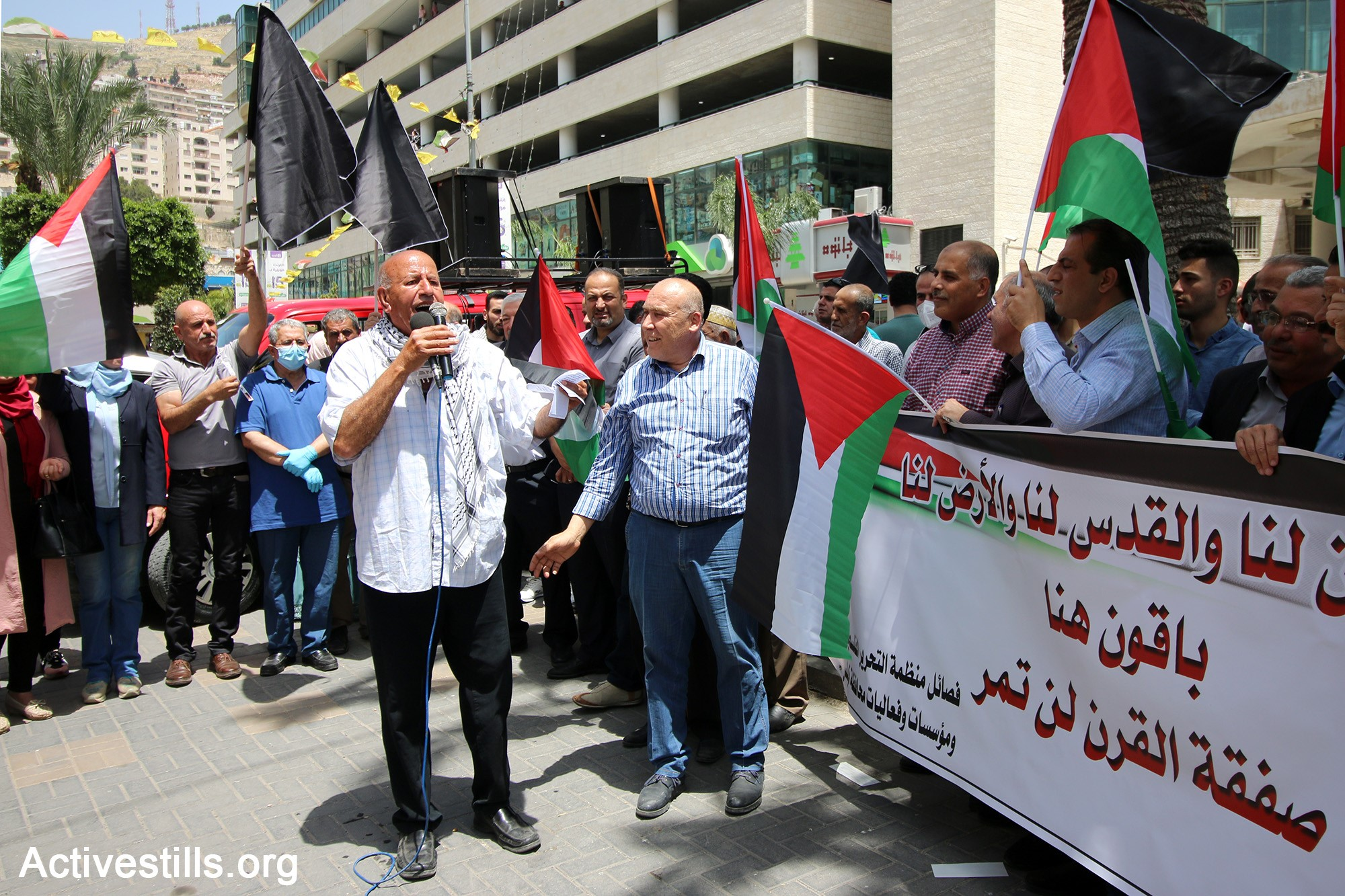 """Palestinians protest in Nablus against Israel's plans to annex parts of the occupied West Ban, May 14, 2020. The large banner reads, in part """"… Jerusalem is ours and the land is ours; [We are ] staying here; the [US-Israeli] 'Deal of the Century' will not pass."""""""