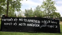 "Demonstrators hold a vigil against annexation opposite the US Consulate in West Jerusalem, May 16, 2020. The Hebrew and English slogans are the same; in Arabic the messages are ""Apartheid will fall"" and ""No to the Judaizing of Jerusalem."""