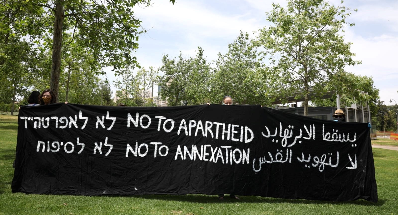 """Demonstrators hold a vigil against annexation opposite the US Consulate in West Jerusalem, May 16, 2020. The Hebrew and English slogans are the same; in Arabic the messages are """"Apartheid will fall"""" and """"No to the Judaizing of Jerusalem."""""""