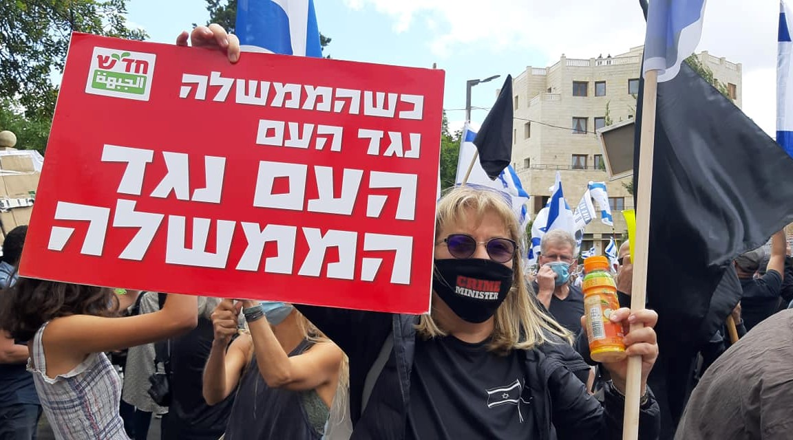 """Demonstrators from the Black Flag and Crime Minister movements gathered in Jerusalem's Paris Square on Sunday, May 24, near the official residence of the prime minister on Balfour Street. The Hadash placard reads: """"When the government is against the people, the people are against the government."""""""