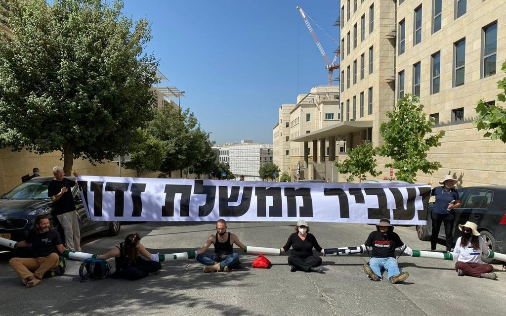 """Demonstrators from the """"Crime Minister"""" movement block the entrance to the offices of Israel's Foreign Ministry in Jerusalem, the venue of the weekly cabinet meeting, Sunday, June 7. The banner paraphrases a passage from a Jewish High Holiday prayer that speaks about """"removing evil government"""" from the world."""
