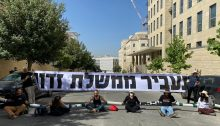 "Demonstrators from the ""Crime Minister"" movement block the entrance to the offices of Israel's Foreign Ministry in Jerusalem, the venue of the weekly cabinet meeting, Sunday, June 7. The banner paraphrases a passage from a Jewish High Holiday prayer that speaks about ""removing evil government"" from the world."