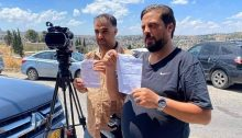 Palestinian TV crew members display orders issued by the Israeli police to report for questioning by law enforcement officers, June 3, 2020.