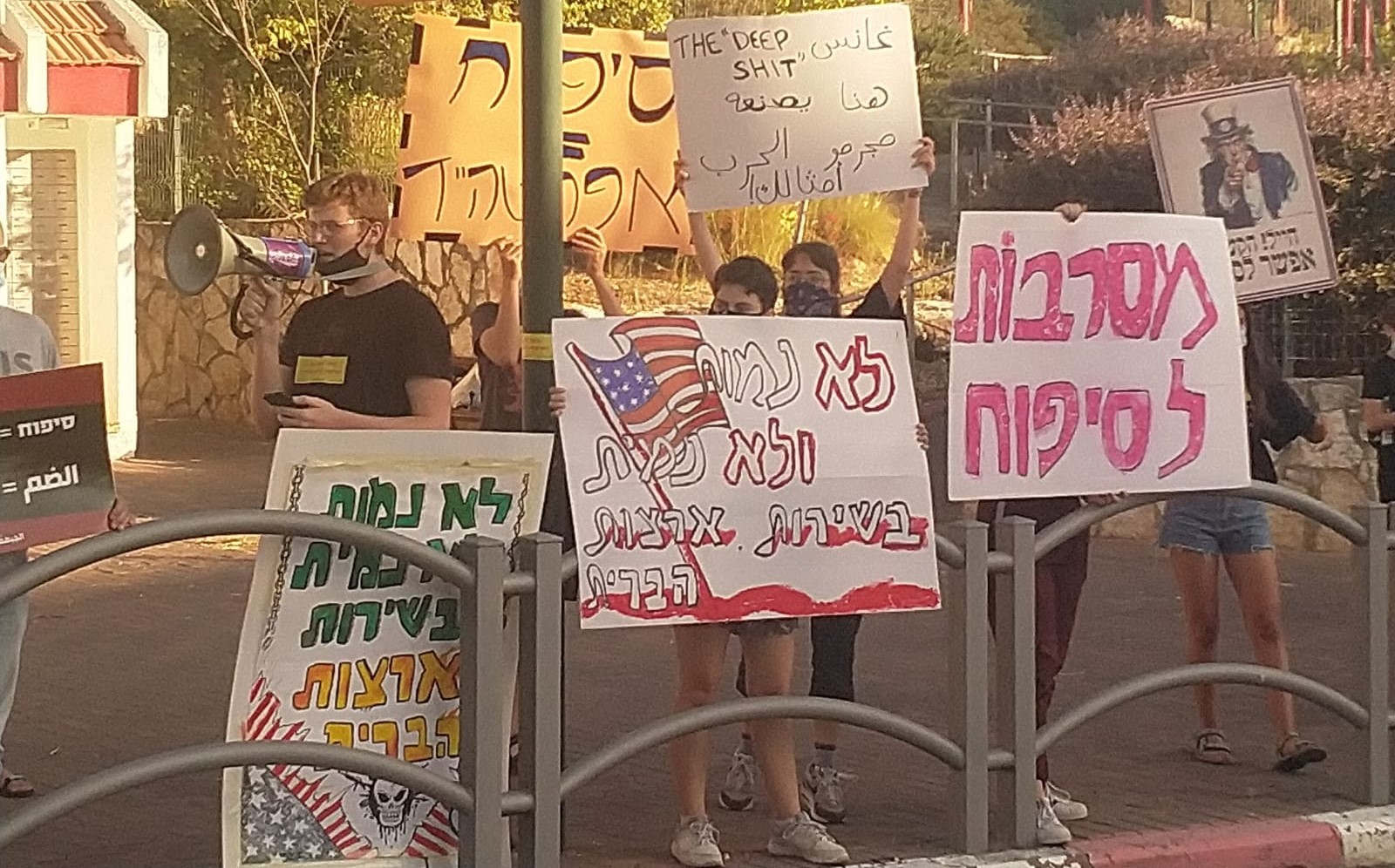 "Members of the group ""Youth against Annexation"" demonstrate near the home of Israel's Minister of Defense, Benny Gantz, in Rosh HaAyin on Thursday, June 25. The placard in Hebrew in the right foreground reads: ""Rejecting Annexation."" The one with the American flag in the center, like that to the left reads: ""We won't die and we won't kill in the service of the United States."" The sign in Arabic (and English) held aloft in the center echoes the American profanity Gantz used earlier in the week when referring to the situation the Palestinians have allegedly made for themselves by refusing to enter into a dialog regarding the looming annexation, and reads: ""The 'deep s**t' made here by war criminals like you is receding!"""