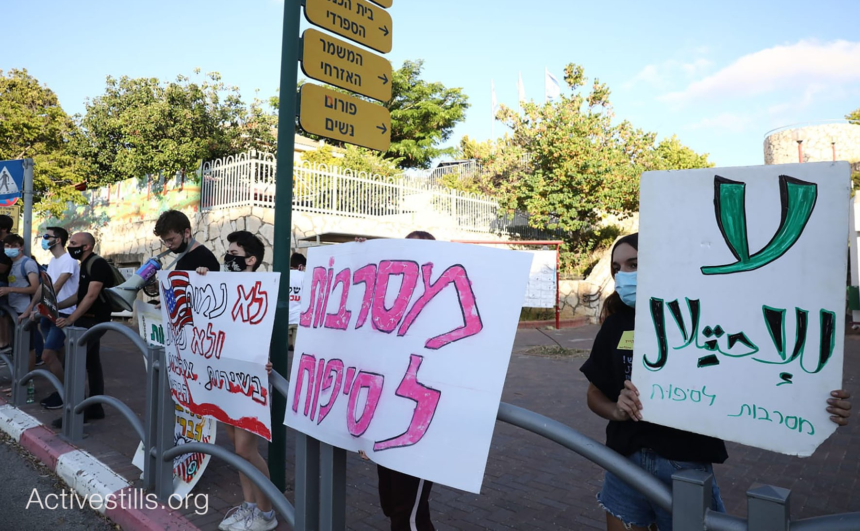 """Members of the group """"Youth against Annexation"""" demonstrate near the home of Israel's Minister of Defense, Benny Gantz, in Rosh HaAyin on Thursday, June 25. The placard at the right reads in Arabic """"No to the Occupation"""" and is signed in Hebrew, """"Rejecting Annexation,"""" a slogan repeated in the two-word placard next to it. The sign with the American flag to the left reads in Hebrew: """"We won't die and we won't kill in the service of the United States."""""""