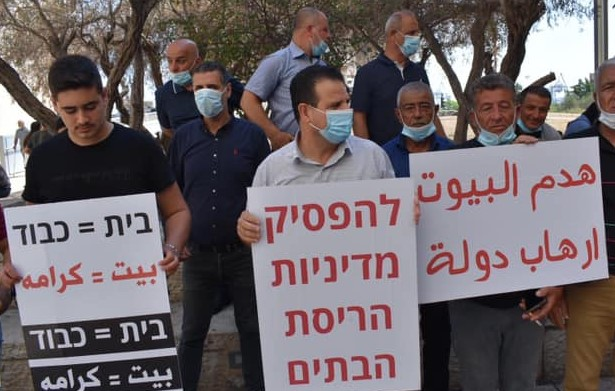 """MK Ayman Odeh, center, participated in a demonstration held in Haifa on Thursday, July 2, against house demolitions in the northern Arab town of Nahef. The placard in Hebrew Odeh is holding reads: """"Halt the Policy of House Demolitions."""" The sign at the right reads in Arabic: """"House Demolitions are State Terror."""" The placard at the left reads in both Hebrew and Arabic: """"Home = Dignity."""""""