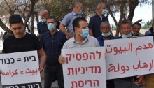 "MK Ayman Odeh, center, participated in a demonstration held in Haifa on Thursday, July 2, against house demolitions in the northern Arab town of Nahef. The placard in Hebrew Odeh is holding reads: ""Halt the Policy of House Demolitions."" The sign at the right reads in Arabic: ""House Demolitions are State Terror."" The placard at the left reads in both Hebrew and Arabic: ""Home = Dignity."""