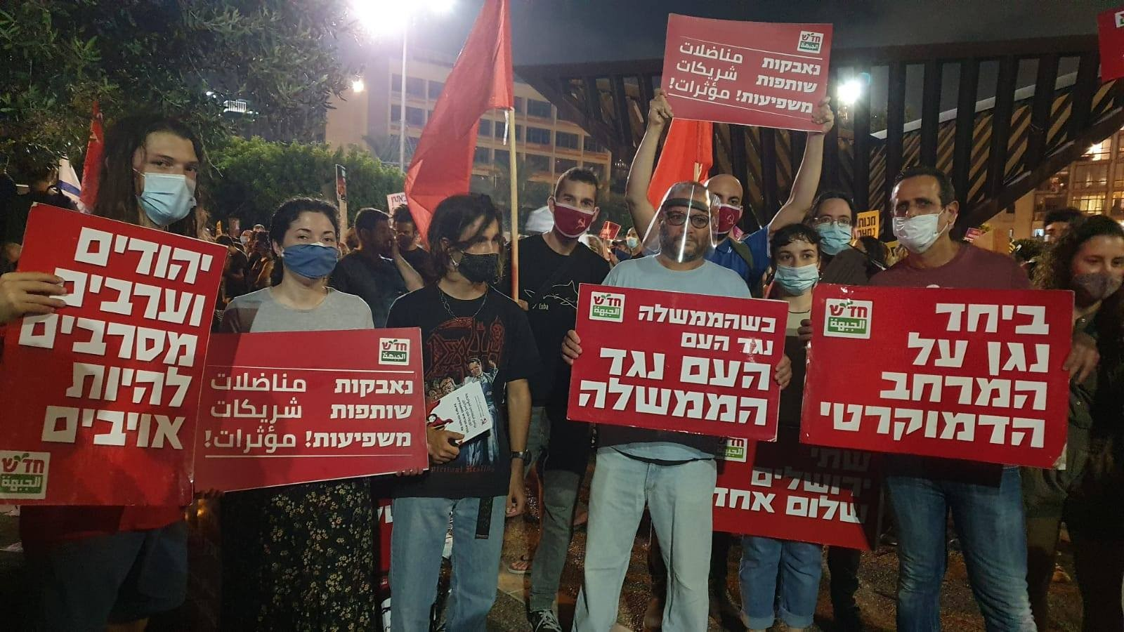 "Activists and supporters of Hadash, among them MK Ofer Cassif (fourth from left), demonstrate against the neoliberal handling of the coronavirus economic crisis by Israel's far-right government, Saturday night, July 11, at Rabin Square in Central Tel Aviv. From right to left the Hadash placards read"" ""Together we'll defend the democratic space""; ""When the government is against the people, the people are against the government""; ""Struggling, Participating and Influencing""; ""Jews and Arabs refuse to be enemies."""