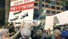 "Tens of thousands of protesters demonstrated in Tel Aviv against the ""Nation-State Law"" in August 2018. The placard held aloft in the foreground reads in Hebrew: ""The Nation-State Law – Formal Apartheid""; in Arabic it reads: ""Down with the Nation-State Law."""