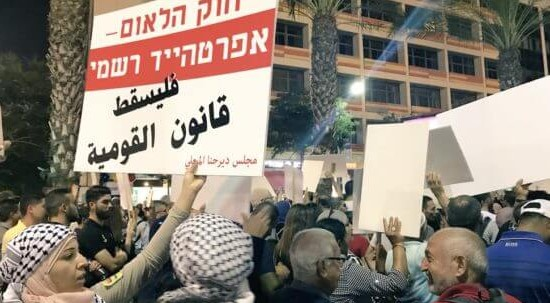 """Tens of thousands of protesters demonstrated in Tel Aviv against the """"Nation-State Law"""" in August 2018. The placard held aloft in the foreground reads in Hebrew: """"The Nation-State Law – Formal Apartheid""""; in Arabic it reads: """"Down with the Nation-State Law."""""""