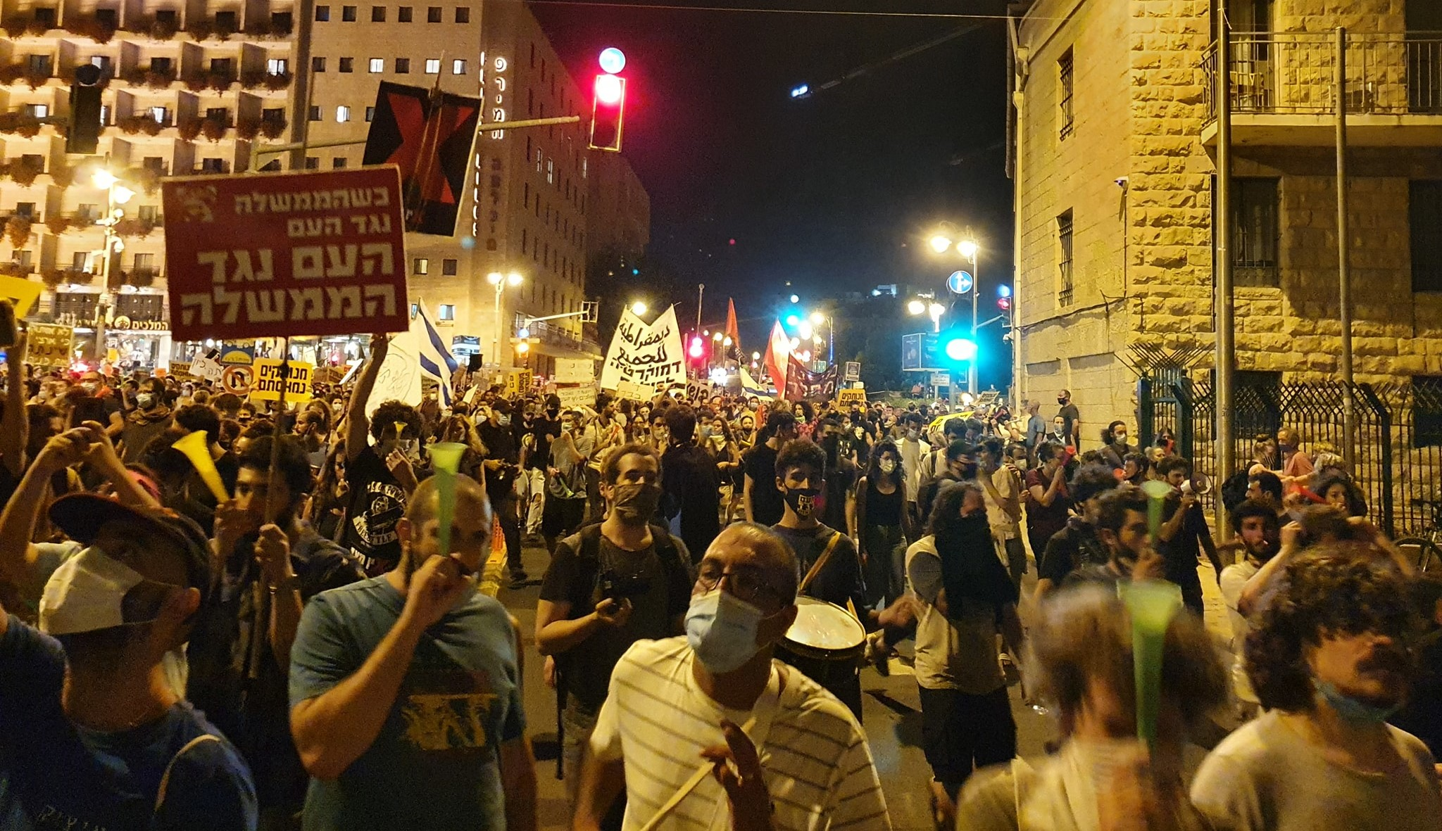"""Thousands of Israelis protested against Prime Minister Benjamin Netanyahu in Paris Square near his official residence in Jerusalem, Saturday July 18. The red Hadash placard in the foreground reads: """"When the government is against the people, the people are against the government."""""""