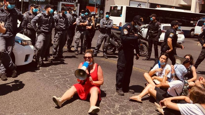 Striking social workers conduct a sit-in on Dizengoff Street in Central Tel Aviv, last Friday, July 17. The demonstrator with the megaphone is the head of the Social Workers' Union, Inbal Hermoni.