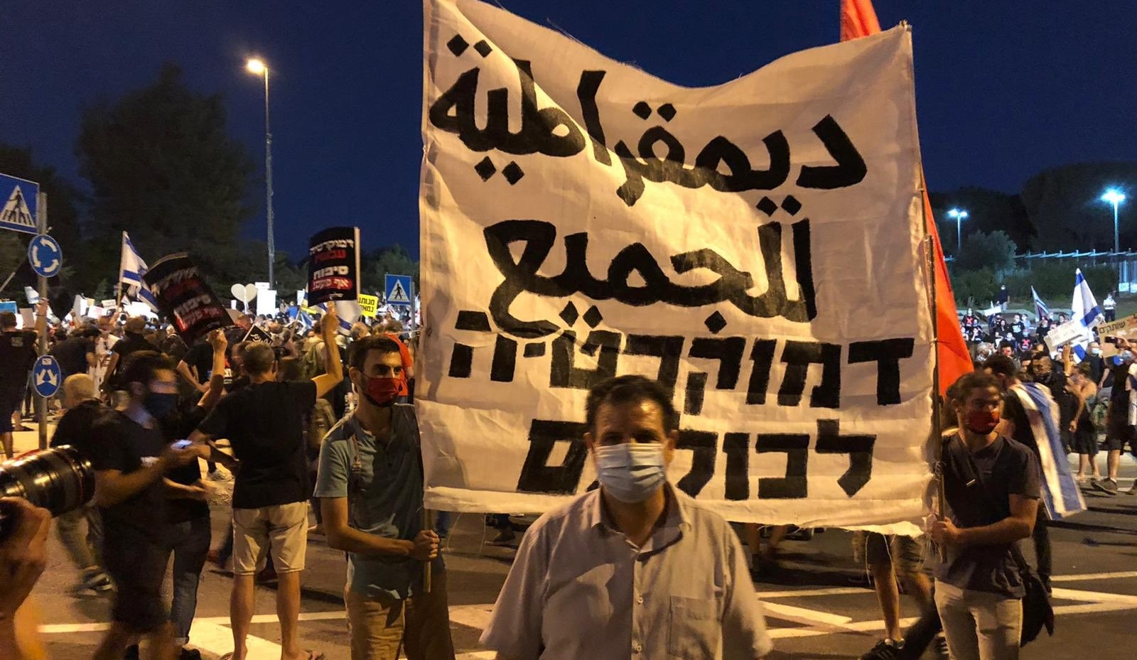 """Joint List leader, MK Ayman Odeh, during the Jerusalem demonstration against Prime Minister Netanyahu on Tuesday, July 21, 2020. The banner in Arabic and Hebrew reads """"Democracy for all."""""""