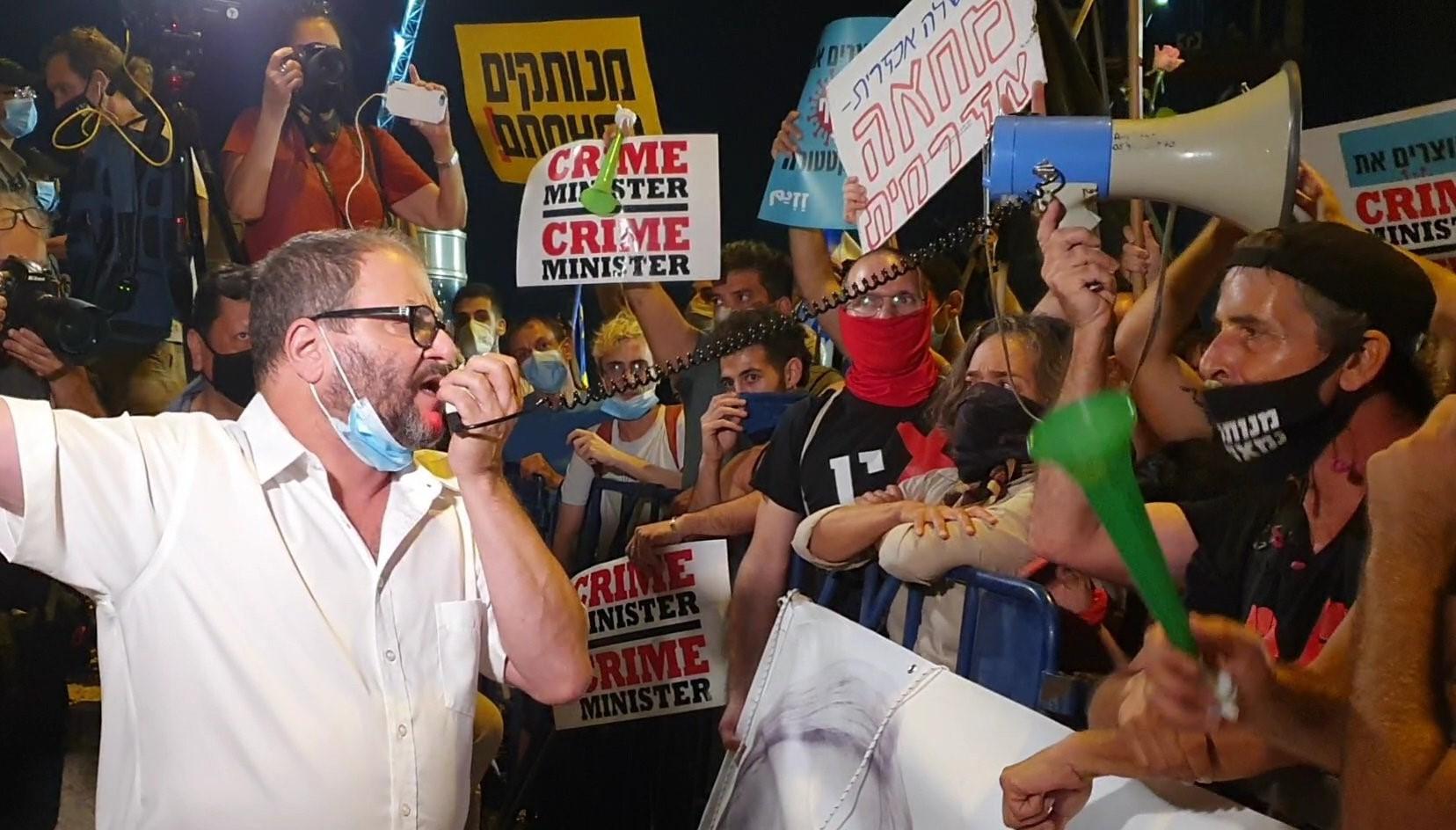 Joint List MK Ofer Cassif (Hadash) addresses demonstrators protesting against Prime Minister Netanyahu in Jerusalem on Tuesday, July 21.