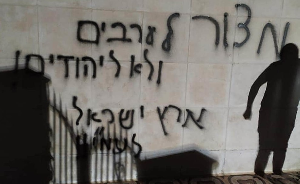 """Graffiti on an outer wall of the torched mosque in Al-Bireh reads """"Siege on Arabs, not on Jews"""" and """"the Land of Israel belongs to the people of Israel."""""""