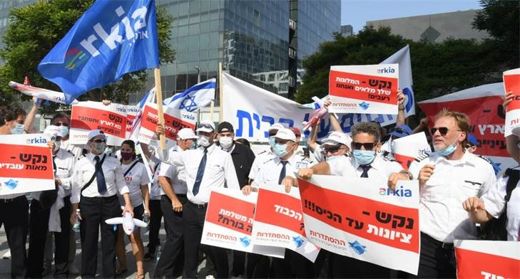 "Workers from Israel's Arkia Airlines demonstrated in Herzliya last Wednesday, July 29, demanding resumption of the service by their employer. The Histradrut union produced signs held by the protestors are all directed to ""Nakash,"" the family name of the three brothers whose group owns the airline and numerous other enterprises. In the front line at the right the text reads: ""Nakash – Zionism until [it comes to reaching into your] pocket!!!""; Behind this, the poster being held aloft reads: ""Nakash – Your hotels are full but we are hungry!"""
