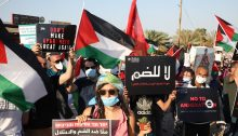 """Palestinian and Israeli activists protest against the Israeli occupation and annexation plans at Almog junction, north of the Dead Sea, an area at risk being annexed, June 28, 2020. The dual language sign held in the foreground reads: """"Together against the annexation and the occupation."""""""