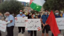 "Members of the CPI hold a vigil in Nazareth in solidarity with the victims of the Beirut port explosion, Tuesday, August 4, 2020. The sign in the center reads: ""Peace for Beirut, from my heart."" The sign to the left of the first reads ""Lebanon – Beirut."""