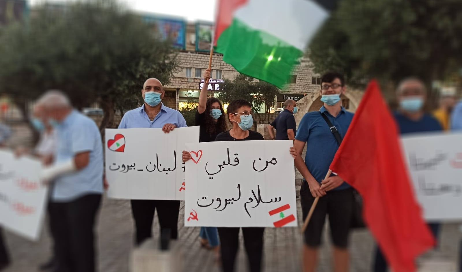 """Members of the CPI hold a vigil in Nazareth in solidarity with the victims of the Beirut port explosion, Tuesday, August 4, 2020. The sign in the center reads: """"Peace for Beirut, from my heart."""" The sign to the left of the first reads """"Lebanon – Beirut."""""""