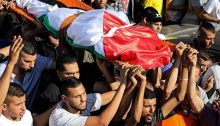 The body of 23-year-old Dalia Samoudi, shrouded in a Palestinian flag, is brought to burial on Friday, August 7, in the Palestinian city of Jenin in the northern West Bank.