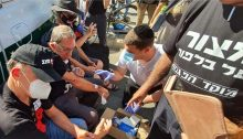 A paramedic treats Carmi Gillon, a former head of the Shin Bet security service, at the protest encampment outside the Prime Minister's Residence in Jerusalem on Thursday August 20, 2020. Gillon's hands and arms were scratched and bloodied in confrontations with police ordered to clear out the encampment to allow Netanyahu supporters demontrate there later in the day.