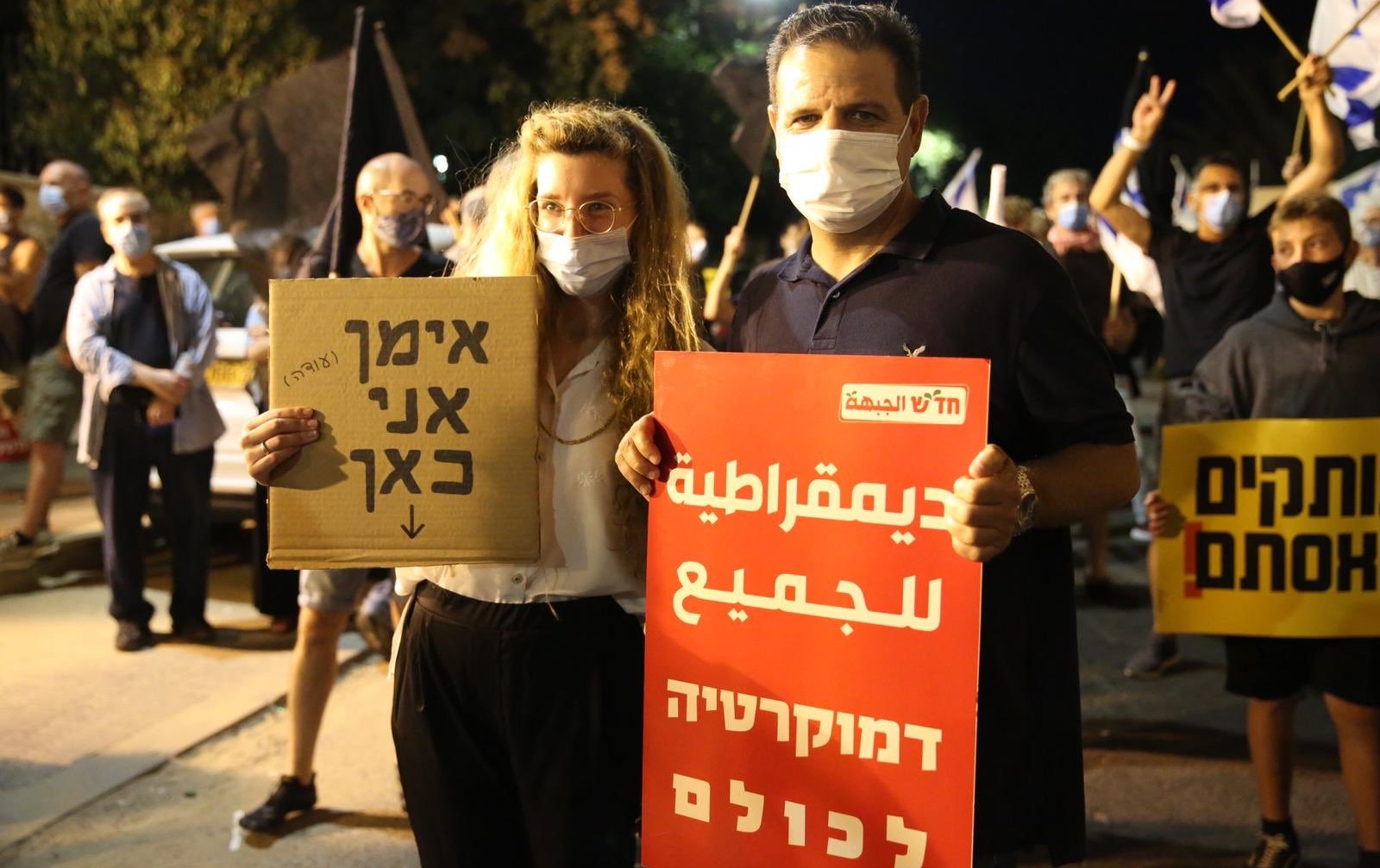 """MK Ayman Odeh holds a Hadash placard that reads in Arabic and Hebrew """"Democracy for all"""" during the anti-government protest in Paris Square, near the PM's official residence, on Saturday night, August 22. The women protester next to Odeh holds a sign in Hebrew reading """"Ayman, I'm here."""""""