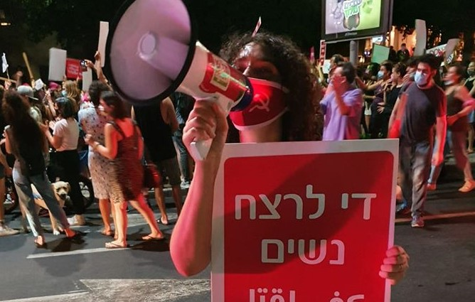 """Noa Levy, a member of the Communist Party of Israel's Central Committee during the protest held in Tel Aviv, August 23, 2020. The placard she's holding reads """"Enough murder of women."""""""