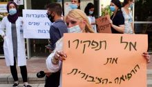 "Medical lab workers demonstrate at Sheba Hospital, Tel Hashomer, August 11, 2020. The sign in the foreground reads: ""Don't abandon public medical care."""