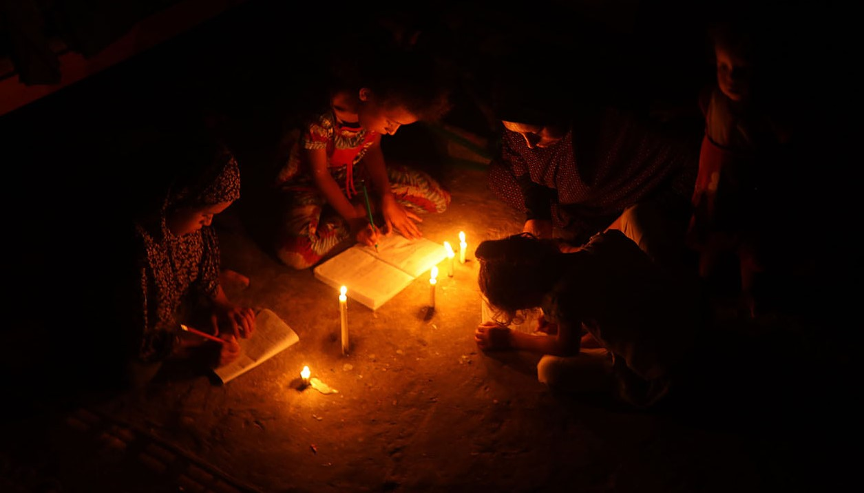 Palestinian children use candles to do their homework in an impoverished household in Khan Yunis in the southern Gaza Strip.