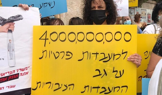 """Public lab workers demonstrate outside of the Prime Minister's official residence in Jerusalem on the third day of their strike, Tuesday, September 1. The placard reads """"4 billion [shekels] to private laboratories on the backs of the public labs."""""""
