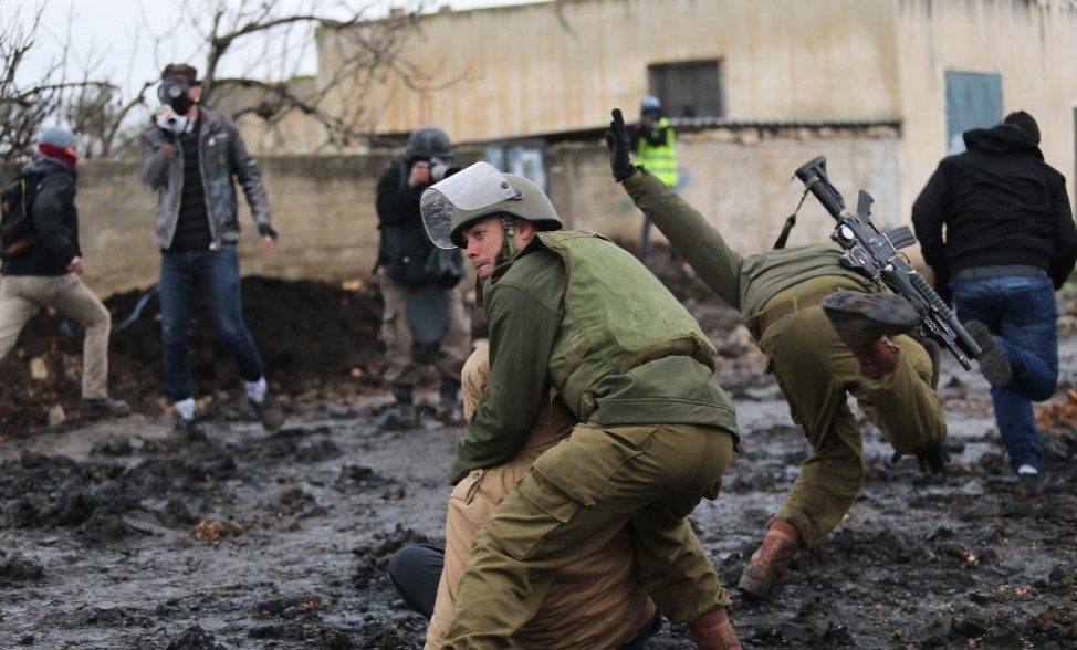 An Israeli soldier slips in the mud as another soldier arrests a Palestinian youth during Kafr Qadum's weekly protest, January 16, 2015.