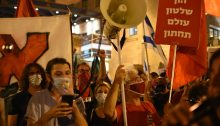 "Activists from Hadash and Communist Party of Israel brandish red flags outside far-right Prime Minister Benjamin Netanyahu's official residence in Jerusalem, Saturday night, September 5. The red sign at the right reads: ""[The combination of ] Capital [and] government are an underworld."""