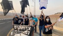 """Members of the Black Flag movement demonstrate against Netanyahu towards evening on Thursday, September 17, at Grofit, near Eilat in the Arabah Desert. The black sign reads: """"Disconnected, Enough of You."""""""