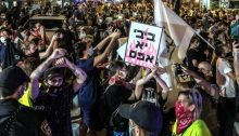 """Police attempt to stop the demonstration on Ben Yehuda Street in Central Tel Aviv on Wednesday night, September 30. The small sign in the foreground reads: """"Bibi, you're a nothing."""""""