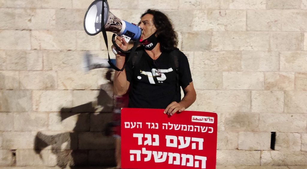 "Leading protest activist Sadi Ben-Shitrit at the demonstration at Jerusalem's Paris Square Wednesday evening, September 30, near the official residence of Prime Minister Benjamin Netanyahu whose resignation the protestors called for. The red Hadash placard reads"" When the government is against the people, the people are against the government."""