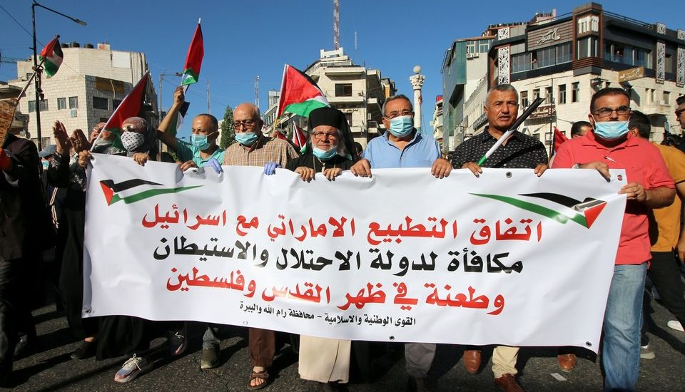 "Palestinians protest against the ""Arab normalization"" in Ramallah, West Bank, following the signing of the US-Israeli-UAE deal, August 15, 2020. The banner reads ""The UAE's normalization agreement with Israel is a reward for the occupation and settlement state and a stab in the back of Jerusalem and Palestine,"" and is signed ""The National and Islamic Forces – Ramallah and al-Bireh Governate."""